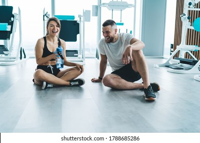 Portrait of cheerful caucasian couple in love having conversation on break in gym satisfied with spending time on active hobby together, happy woman laughing at funny jokes of boyfriend resting in gym