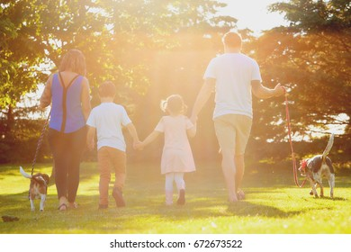 Portrait of cheerful Caucasian family with two children walking together with dogs holding hands and communication in summer park