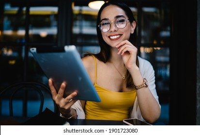 Portrait of cheerful Caucasian female blogger in eyewear smiling at camera during time for online networking via digital tablet, joyful hipster girl with modern touch pad posing in street cafe