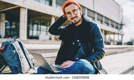 Portrait of cheerful caucasian male remote worker dressed in stylish clothing smiling at camera while sitting with laptop device on publicity area, concept of modern technology and communication