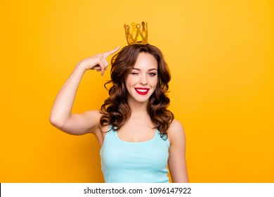 Portrait of cheerful charming girl showing gold crown on head with forefinger winking with one eye looking at camera isolated on yellow background