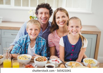 Portrait of cheerful children and parents having breakfast by table at home
