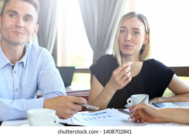 Portrait of cheerful corporate workers in cafe. Beautiful female with gorgeous manicure wearing trendy black dress. Handsome man in blue shirt looking away with smile and joy. Restaurant interior