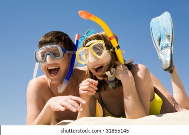 Portrait of cheerful couple in aqualungs lying on sand and laughing