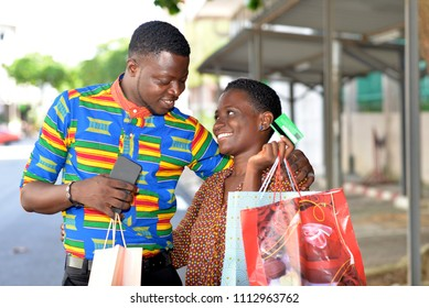 Portrait of cheerful couple with shopping bags and credit card outdoors.concept and shopping.