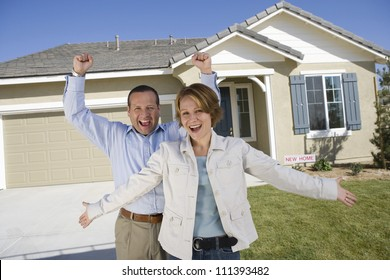 Portrait of cheerful couple standing in front of new house