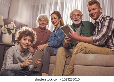Portrait of cheerful curly son playing with gadget. Glad granny, adult daughter with bearded husband and granddad sitting on sofa. Generation concept