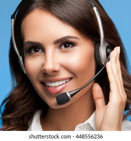Portrait of cheerful customer support female phone operator in headset, over blue background