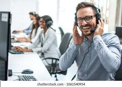 Portrait of cheerful customer support telephone operator in call centre