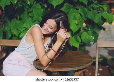 Portrait of a cheerful cute woman listening music in headphones