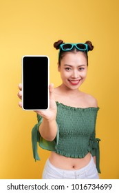 Portrait of a cheerful cute woman showing blank smartphone screen isolated over yellow background