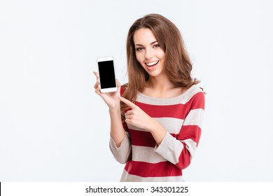 Portrait of a cheerful cute woman showing blank smartphone screen isolated on a white background