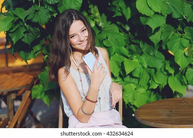 Portrait of a cheerful cute woman with smart phone