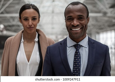 Portrait of cheerful cute young businessman and businesswoman in formal clothes are standing together and looking at camera with joy. Focus on african man