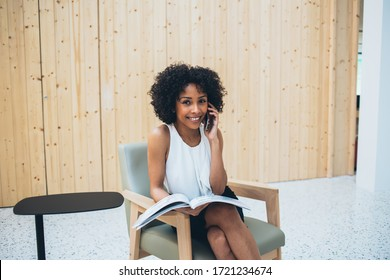 Portrait of cheerful dark skinned female entrepreneur smiling at camera during positive smartphone conversation and time for reading literature book, happy woman calling to friend via app on cellphone