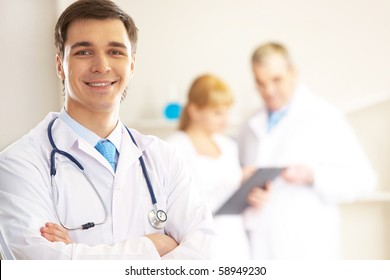 Portrait of cheerful doctor looking at camera and smiling with working clinicians behind