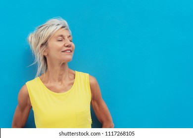 Portrait of cheerful dreamy mature blonde woman wearing yellow dress posing against blue background
