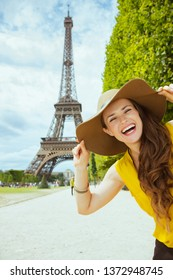 Portrait of cheerful elegant solo traveller woman in yellow blouse and hat against clear view of the Eiffel Tower in Paris, France.