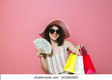 Portrait of cheerful elegant young woman in sunglasses holding fan of money and colorful shopping bags, isolated over pink background