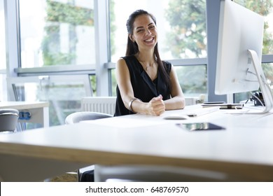Portrait of cheerful employer of business enterprise enjoying creative working process in modern office indoors, young administrative manager satisfied with occupation planning project using computer