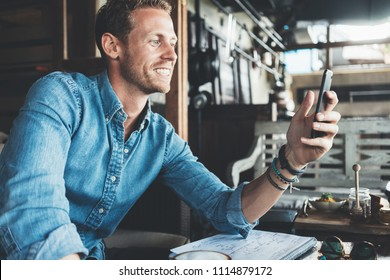 Portrait of cheerful entrepreneur working on his project at street cafe, using cell phone