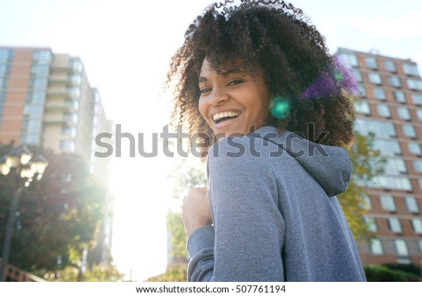 Portrait of cheerful ethnic girl in town
