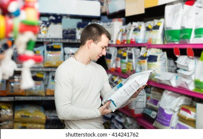 Portrait of cheerful european guy selecting vet food in petshop
