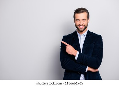 Portrait of cheerful excited joyful satisfied handsome attractive fashionable macho guy dressed in formal outfit dark velvet pointing on empty blank copyspace isolated on gray background copy-space
