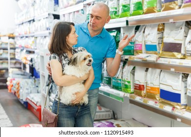 Portrait of cheerful family couple with dog selecting vet food in petshop