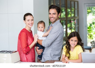 Portrait of cheerful family at desk in home