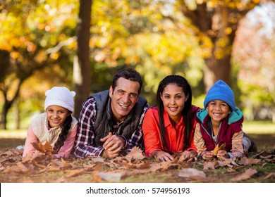 Portrait of cheerful family lying on field at park during autumn
