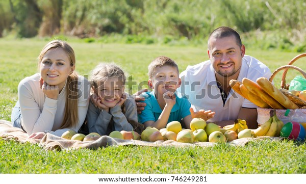 Portrait of cheerful family lying in the park