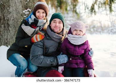 Portrait cheerful family relaxing sitting under the spruce forest in winter. Family of three