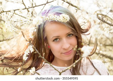 Portrait of cheerful fashionable woman in spring blooming tree, with flowers in hair, retro vintage color