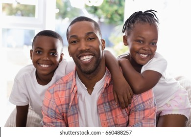 Portrait of cheerful father and children sitting on couch at home