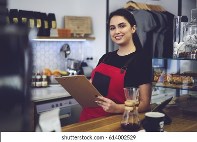 Portrait of cheerful female cafeteria staff member ready to start working due to contract dressed in apron uniform, smiling administrative manager counting annual income from service and sales