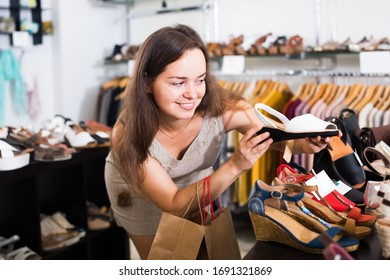 Portrait of cheerful female customer selecting shoes in footgear center
