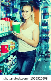 portrait of cheerful female customer taking paint can in housewares department