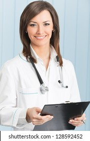 Portrait of cheerful female doctor with clipboard at office