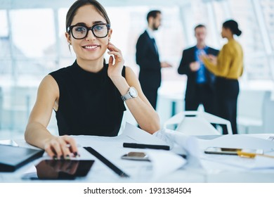 Portrait of cheerful female manager in formal outfit doing office job and smiling at camera, successful Caucasian woman boss in optical eyewear for vision correction posing at table desktop