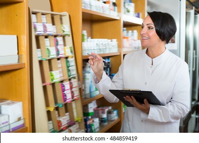 Portrait of cheerful female pharmacist with clipboard in hands working in healthy food store