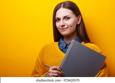 Portrait of cheerful female student with book in hand on a yellow background