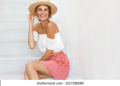 Portrait of cheerful female in stylish top, polka dot skirt and straw hat poses at white stairs, going to have walk at beach, expresses positiveness. People, summer, lifestyle and beauty concept