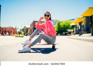 Portrait of cheerful female teenager in stylish sunglasses resting at longboard during sport hobby in city, happy Asian hipster girl 20s enjoying recreation chill posing at girlish skateboard