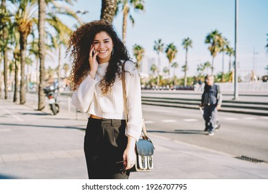 Portrait of cheerful female tourist with curly hair smiling at camera while using cellphone technology for friendly calling, happy girl enjoying international conversation for talking with family