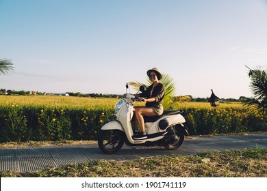 Portrait of cheerful female tourist sitting on rented vintage moped smiling at camera while getting to travel destination in Vietnam, funny woman in casual clothing ride on motorcy?le on path