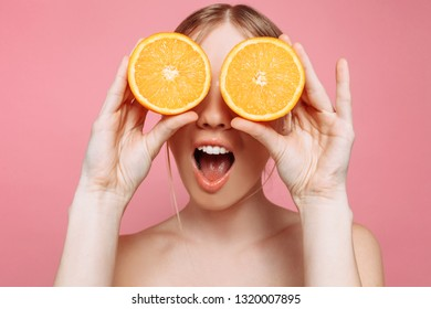 Portrait of a cheerful feminine girl, with natural clear skin, a girl with orange slices, covering her eyes, isolated on a pink background. Skin care concept, natural beauty
