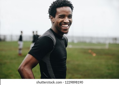 Portrait of a cheerful footballer standing on field during practice. Side view of an african soccer player standing on football field practicing in the morning.