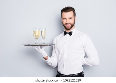 Portrait of cheerful friendly man in classic white shirt and black bow holding hand behind the back and tray with three glasses of champaign, sparkling wine, isolated on grey background