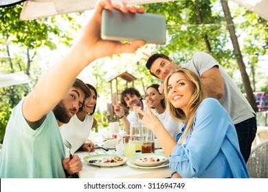 Portrait of a cheerful friends making selfie photo on smartphone in outdoor restaurant
